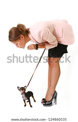 Pretty young woman holding a black Chihuahua on a leash - stock photo