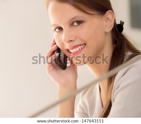 Pretty young woman holding a cell phone - stock photo