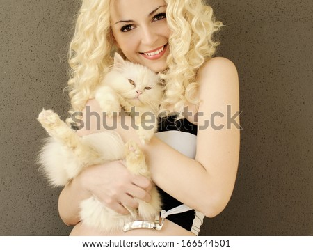 Pretty young woman holding a Persian kitten - stock photo