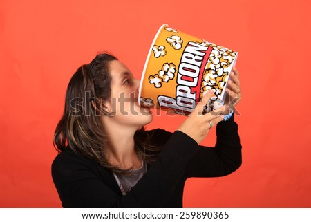 pretty young woman holding a pop corn bowl - stock photo