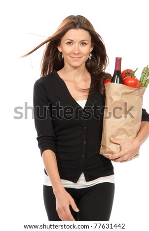 Pretty young woman holding a shopping bag full of vegetarian groceries - stock photo