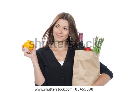 Pretty young woman holding a shopping bag full of vegetarian groceries and orange in hand on a white background - stock photo
