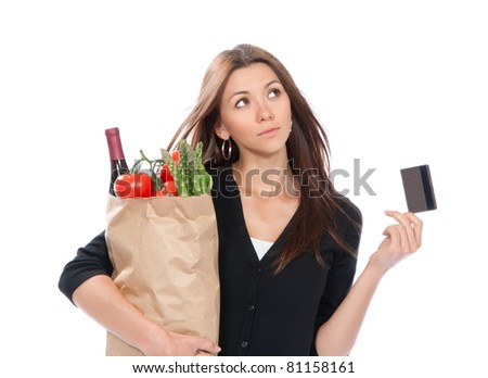 Pretty young woman holding a shopping bag full of vegetarian groceries in supermarket with tomatoes, asparagus, bottle of red wine and credit card isolated on white background - stock photo