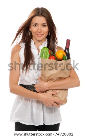 Pretty young woman holding a shopping bag full of vegetarian groceries, tomatoes, salad, bottle of red wine, orange, pepper isolated on white background - stock photo