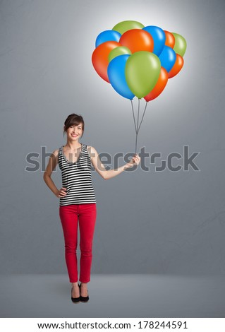 Pretty young woman holding colorful balloons