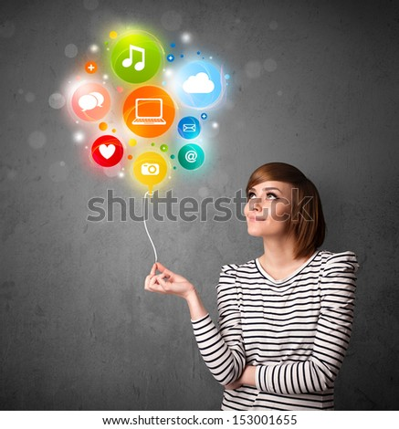 Pretty young woman holding colorful social media icons balloon - stock photo