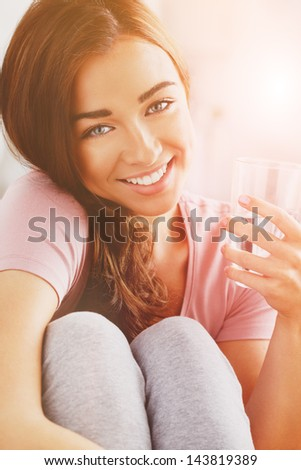 pretty young woman holding glass water smiling - stock photo