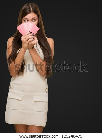 Pretty Young Woman Holding Playing Cards against a black background - stock photo
