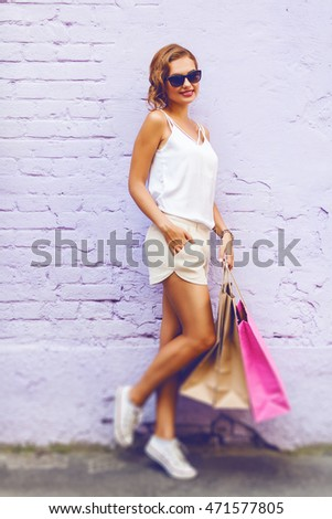 Pretty young woman holding shopping bags against a brick wall
