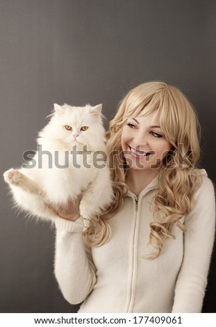 Pretty young woman holding white Persian cat - stock photo