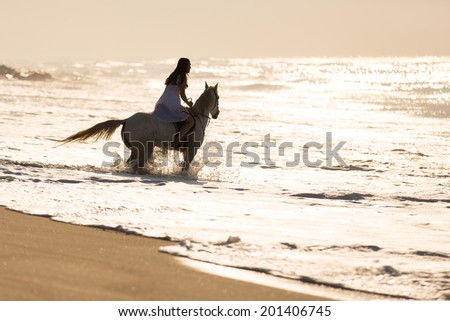 pretty young woman horse ride on the beach