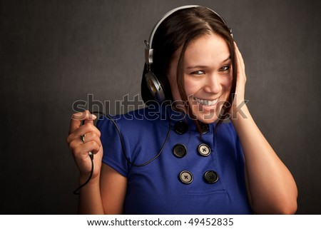 Pretty young woman in a blue dress with Headphones - stock photo