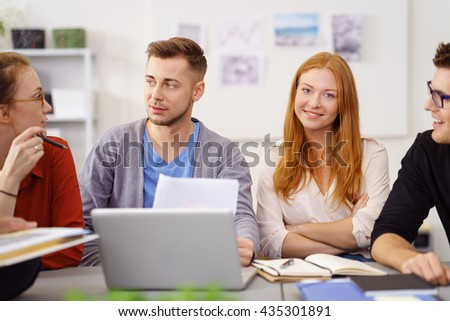 Pretty young woman in a business meeting with her office co-workers sitting in the centre at a table smiling at the camera - stock photo