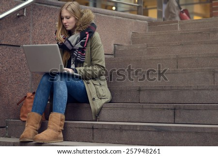 Pretty young woman in a smart casual winter outfit sitting on steps in town with a laptop on her knees as she accesses the internet or studies her class project via e-learning