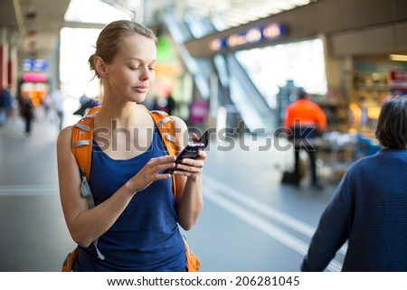 Pretty, young woman in a trainstation, waiting for her train, boarding a train (color toned image) - stock photo