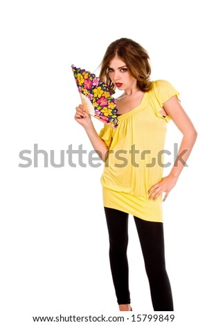 Pretty young woman in a yellow dress and black leggings with a floral patterned fan