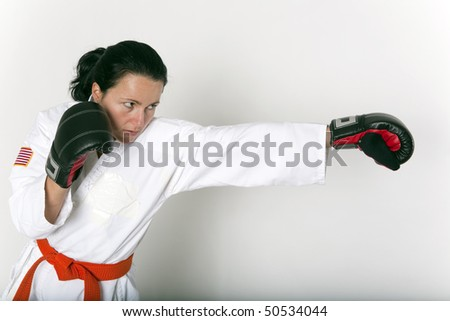 Pretty young woman in an attack/punching stance wearing a martial arts uniform and boxing style gloves. - stock photo