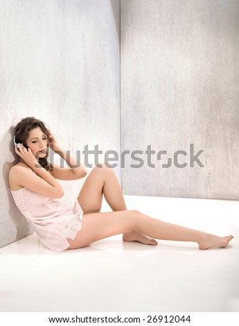 Pretty young woman in an empty room listening music - stock photo