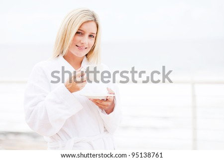 pretty young woman in bathrobe drinking tea on balcony