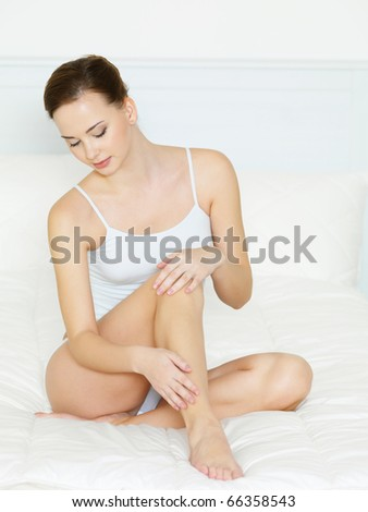 Pretty young woman in bedroom touching her beautiful legs - indoors - stock photo