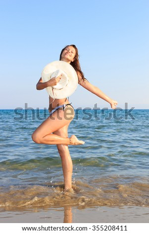 Pretty young woman in bikini on the tropical beach - stock photo