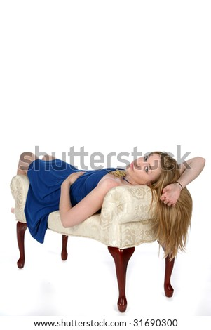 pretty young woman in blue relaxing on bench - stock photo