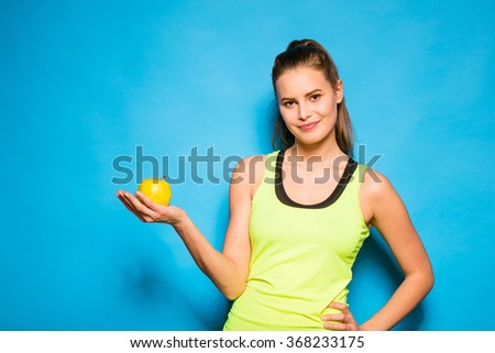 pretty young woman in fitness equipment having and green apple in hand on blue background - stock photo