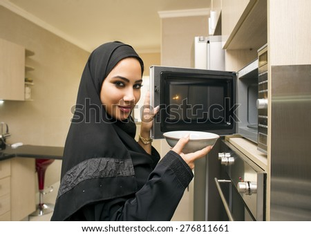 Pretty young woman in kitchen using microwave oven - stock photo