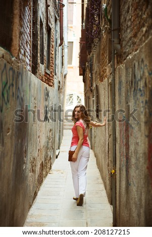 Pretty young woman in narrow Venice street - stock photo