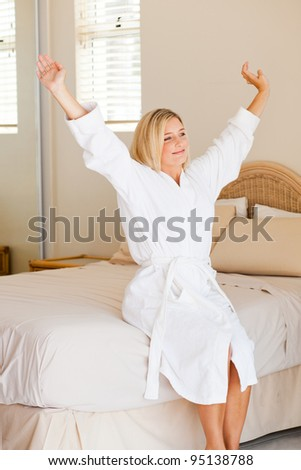 pretty young woman in pajamas just wake up and stretch on bed