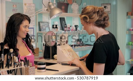 Pretty young woman in perfumery shop choose cosmetics with cosultant