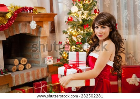 Pretty young woman in red and white christmas dress and long beautiful hair, holding a gift boxes near chimney and Christmas tree over living room. - stock photo