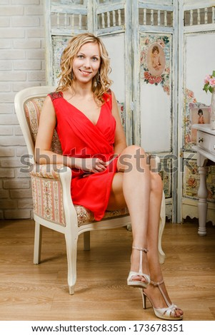 Pretty young woman in red dress sitting on vintage armchair in retro style - stock photo