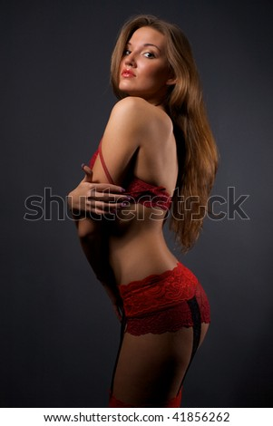 Pretty young woman in red lingerie and stockings standing in the studio