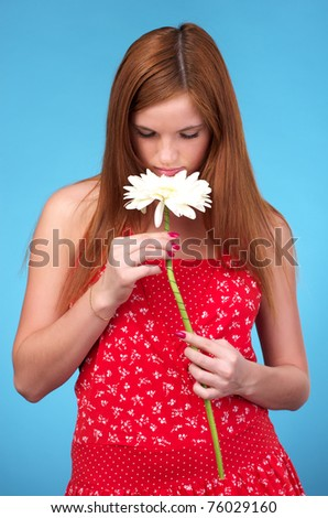 Pretty young woman in red sun-dress sniffing white flower - stock photo