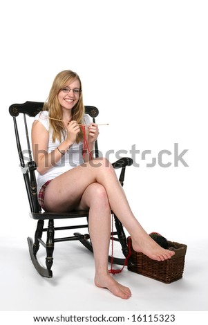 pretty young woman in rocking chair knitting - stock photo