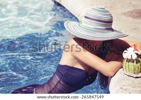 Pretty young woman in sexy bikini at edge of a swimming pool with exotic cocktail. Girl at travel spa resort pool. Summer luxury vacation. - stock photo