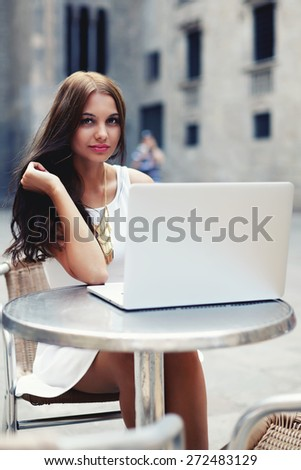 Pretty young woman in summer dress sitting at sidewalk cafe with open laptop computer, brunette hair female with open notebook next to her outside in coffee shop, tourist girl using her laptop in city