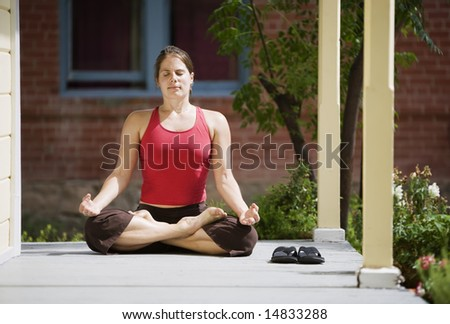 Pretty Young Woman in the Lotus Position on a Porch - stock photo
