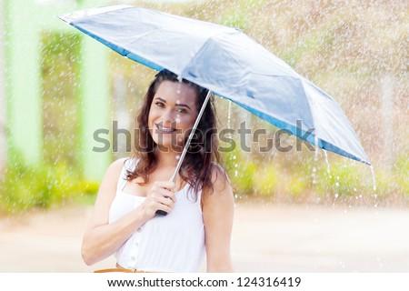 pretty young woman in the rain with umbrella - stock photo