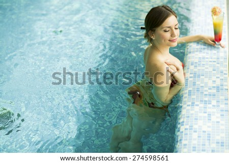 Pretty young woman in the swimming pool - stock photo