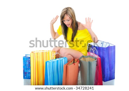 Pretty young woman in very good mood being surrounded with shopping bags - stock photo