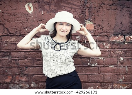Pretty young woman in white blouse and hat posing against brick wall background. Woman holds the edges of the hat by hands. Toned photo with copy space. Vintage style photo. - stock photo