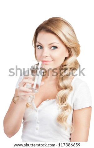 Pretty young woman in white T-short is holding a glass of water. Beautiful blonde long-haired girl is drinking water from glass on white. Studio shot.