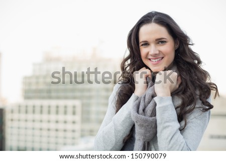 Pretty young woman in winter clothes posing outside on a cloudy day - stock photo