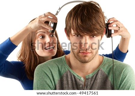 Pretty young woman interrupts man with headphones - stock photo
