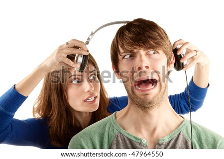 Pretty young woman interupts man with headphones - stock photo