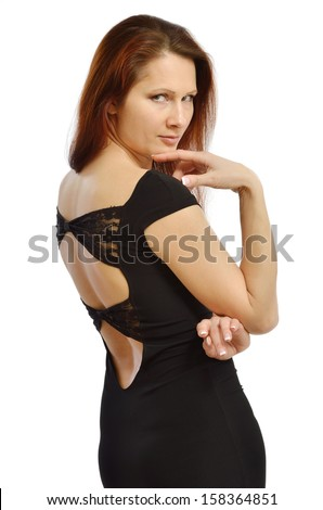 Pretty young woman is looking over shoulder. She is wearing a black cocktail dress with a bare back. - stock photo
