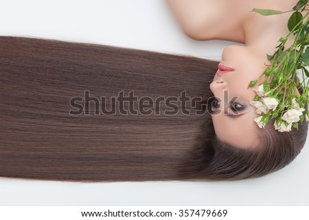 Pretty young woman is lying with her long straight smooth hair. She is looking forward with serenity and relaxing. There are white flowers near her face - stock photo