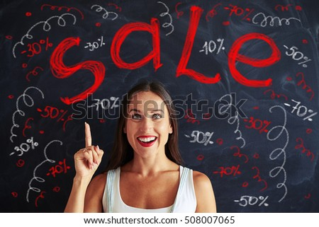 Pretty young woman is pointing up with her finger at red and white chalk sale advertisement on blackboard behind her